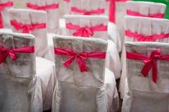 Stoelen voor huwelijksceremonie met witte en roze linten worden verfraaid dat Stock Foto's