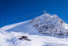 Stoellift en sneeuw groomer in Alpen stock afbeelding