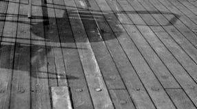 Stoelschaduw op een houten vloer stock foto's