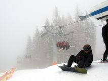 Stoeltjeslift met mensen in mist Snowboarderzitting bij de lift stock foto's