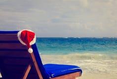 Stoelzitkamer met rode Kerstmanhoed op strand Royalty-vrije Stock Afbeelding