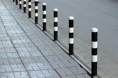 Stoep en weg met veiligheidsmeerpalen wordt in zwart-wit worden geschilderd gescheiden die stock afbeelding