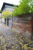 Stoep met gevallen gele bladeren en oude sjofele omheining De straat van Irkoetsk Stock Foto's