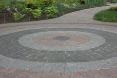 Stoep van graniet van verschillende kleuren in de vorm van een cirkel in de binnenplaats van de kerk Stock Afbeeldingen