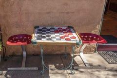 Stoeplijst met de stoelen van de tractorzetel en schaakborddeken met reuzecontroleurs die naast gipspleistermuur en open deuropen royalty-vrije stock fotografie