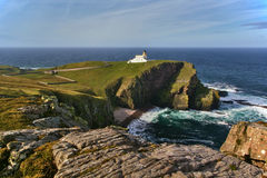Stoer Lighthouse. White lighthouse sitting atop a huge cliff above the shoreline Royalty Free Stock Image