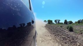 Stof die van het automobiele wielen automobiele drijven op landelijke grintweg toenemen stock video