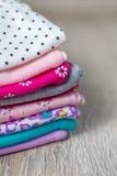 Stof het Naaien Gevouwen roze en witte bodysuit op het grijze houten achtergrond luier voor pasgeboren meisje Stapel van zuigelin stock afbeeldingen