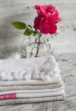 Stoffen katoenen keukenhanddoeken en roze rozen in een glasvaas Stock Fotografie