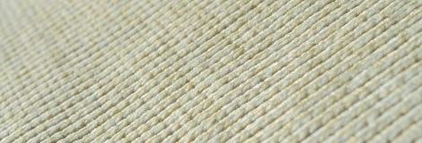 Stoffentextuur van een zachte gele gebreide sweater Macrobeeld van de structuur van banden in garens stock afbeeldingen
