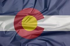 Stoffenvlag van Colorado Vouw van de vlagachtergrond van Colorado, de staten van Amerika royalty-vrije illustratie