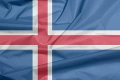 Stoffenvlag van IJsland Vouw van de vlagachtergrond van IJsland royalty-vrije illustratie