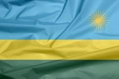 Stoffenvlag van Rwanda Vouw van Rwandese vlagachtergrond stock illustratie