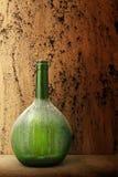 Stoffige die wijnfles tegen grungeachtergrond wordt geplaatst Royalty-vrije Stock Foto's