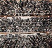 Stoffige wijnflessen in opslag. stock fotografie