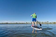 Stoi up paddling na jeziorze Zdjęcia Stock