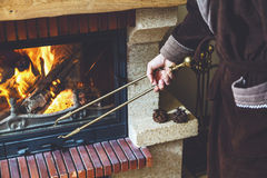 Stoke fireplace. Brass fireplace tongs in hand man Royalty Free Stock Images