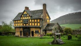 Stokesay slottporthus med gul färg och korsvirkes- specificera och sikt av trädgården på en mulen dag arkivfoton