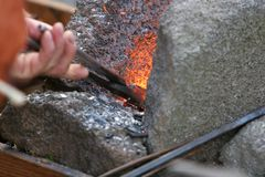 Stoking the fire. A craftsman/blacksmith working metal the oldfashioned way, with hammer and anvil and open fire Royalty Free Stock Photo
