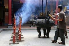 Stokken van de mensen de dragende wierook in Boeddhistische tempel Stock Afbeeldingen