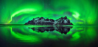 Stokksnes aurora. Aurora reflections on Stokksnes black beach with Vestrahorn mountains in center, Iceland Stock Images