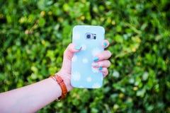 Stokrotka kwiatu telefonu ręka z błękitnymi gwoździami i skrzynka Fotografia Stock