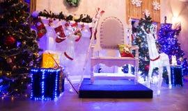 Stol för Santa Claus och askar med gåvor i en hemtrevlig vardagsrum royaltyfri fotografi