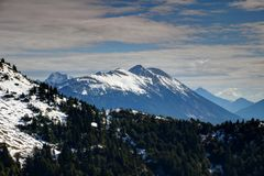 Stol the highest peak of Karavanke with snowy ridges, Slovenia. Snow-capped Stol / Hochstuhl, highest peak of Karavanke / Karawanken mountain range, with pine Royalty Free Stock Photo