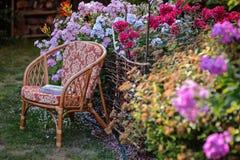 Stol i blommande sommarträdgård Royaltyfri Bild