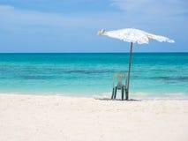Stol och paraply på stranden Royaltyfri Bild