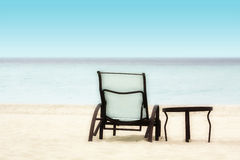 Stol och tabell på stranden Arkivbild