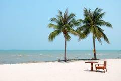 Stol- och tabelluppsättningen på den vita rena sanden sätter på land med kokospalmer och det härliga havet Royaltyfri Bild