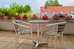 Stol två och en tabell med blommor i en balkong Royaltyfria Foton