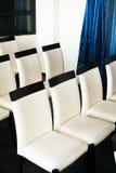 Stolar för vitt läder i en korridor för konferenser och föreläsningar royaltyfria foton