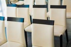 Stolar för vitt läder i en korridor för konferenser och föreläsningar royaltyfri fotografi