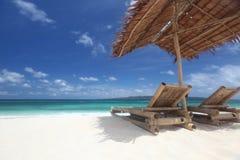 Stolar med slags solskydd på stranden Arkivfoto