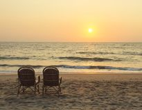 Stolar near kustlinjen på solnedgångtid Royaltyfria Foton