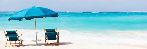 Stolar och paraply på den tropiska stranden Royaltyfria Bilder