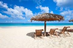 Stolar och paraply på den tropiska stranden Royaltyfri Fotografi