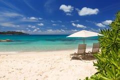 Stolar och paraply på en från Seychellerna härlig tropisk strand Arkivfoto