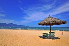 Stolar och paraply på sandstranden royaltyfria foton