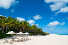 Stolar och paraply på den tropiska stranden Arkivbilder