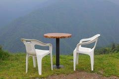 Stolar och tabell framme av berget Fotografering för Bildbyråer