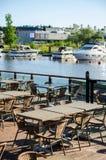 Stolar och tabeller av den lokala restaurangen i hamn med fartyg royaltyfria bilder