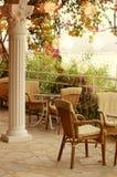 Stolar och tabeller på en tom terrass mot havet och blommorna Royaltyfri Foto