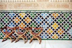 Stolar och väggen av tegelplattor i Alhambraen royaltyfri fotografi