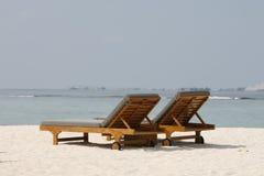 Stolar på en härlig tropisk strand på Maldiverna Royaltyfri Foto