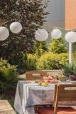 stolar på tabellen med frukter i trädgården med växter och vita lyktor under partiet Verkligt foto fotografering för bildbyråer