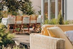 Stolar på tabellen på terrassen av huset med växter och rottingmöblemang under sommar Verkligt foto fotografering för bildbyråer