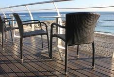 Stolar på terrassen framme av havet Arkivfoto